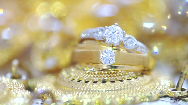Macro shot of wedding rings with golden textured background.