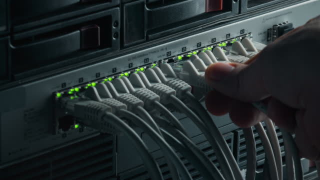 vídeos y material grabado en eventos de stock de macro shot: la persona conecta el conector de internet rj45 en el conmutador de enrutador lan. red de comunicación de información con cables de datos conectados a puertos de módem con luces intermitentes - cable
