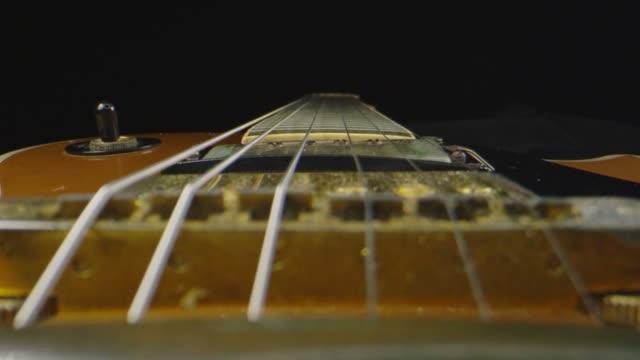 makro sköt genom en elgitarr som lägger ner - akustisk gitarr bildbanksvideor och videomaterial från bakom kulisserna