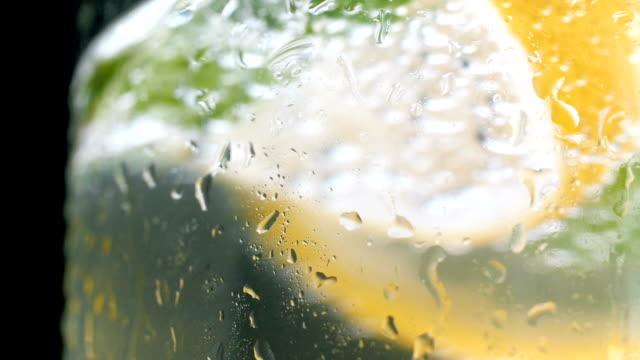 vídeos de stock e filmes b-roll de macro slow motion footage of water prolets on cold glass of lemonade against black background - limonada tradicional