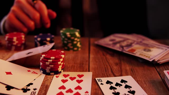 Macro view of poker game where man knocks by finger glass with alcohol and then throws chips