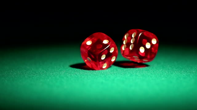 Macro view of red casino dice rolling on table, success video