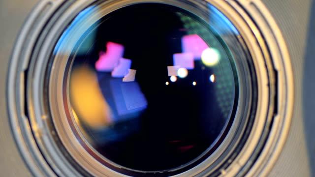 a macro view on a camera lens changing focus. - lente strumento ottico video stock e b–roll