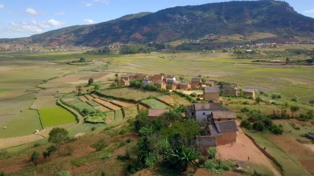 vídeos de stock, filmes e b-roll de aldeia de terras altas de madagascar e exibição de drone de campos de arroz - aldeia