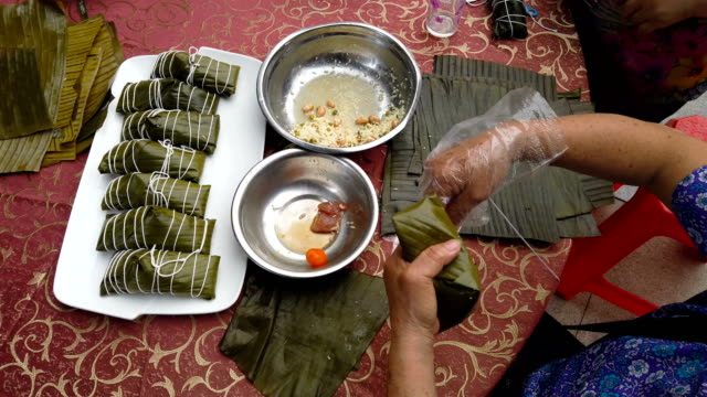 madam making traditional Chinese ZongZi white for Dragon Boat Festival ie DuanWu festival at 4K 60FPS - vídeo