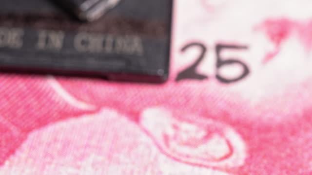 hergestellt in china text auf einem stück plastik über einem yuan-schein geschrieben. - zahl 25 stock-videos und b-roll-filmmaterial