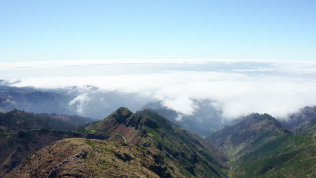 Madeira, portuguese island inland mountain range with running clouds drone aerial 4K footage.