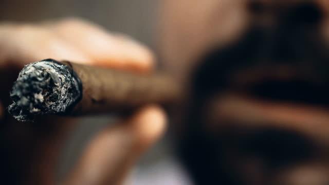 mafioso che espira nuvole di fumo, sbuffa il sigaro e prende decisioni importanti - sigaro video stock e b–roll