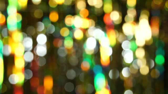 magic abstract shiny background with colored defocused bokeh. beautiful dynamic background in shining lights and sparkling particles. festive mood. christmas or holiday theme - ghirlanda decorazione video stock e b–roll