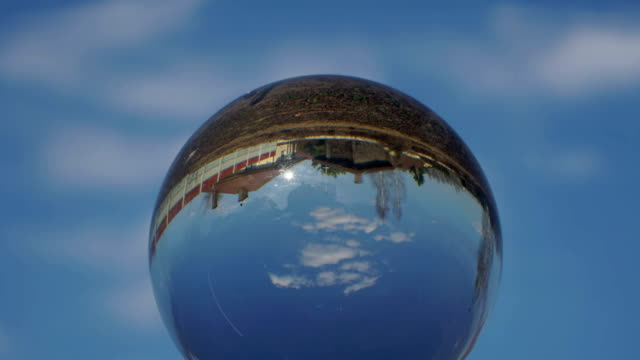 Magic crystal ball with reflection of heaven sky with passing clouds time lapse