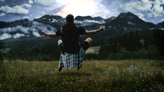 Magic in nature. Man levitating on the meadow Meditation in mountains. Man levitating in lotus pose. Planets, stars and galaxies in background paranormal stock videos & royalty-free footage