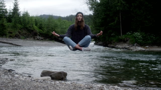 Magic in nature. Woman levitating above the stream Meditation in mountains. Woman levitating in lotus pose paranormal stock videos & royalty-free footage