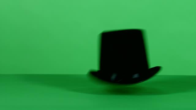 vidéos et rushes de noir chapeau magique chutes sur green à écran plat haute définition - chapeau