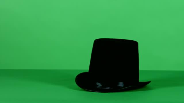 top nero cappello magico ruota su schermo verde - cilindro video stock e b–roll