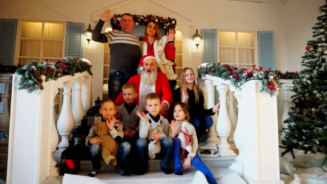 Magical Santa together with caring mother and father of charming children sends greetings to friends relatives on stairs house, beautifully decorated for holidays video
