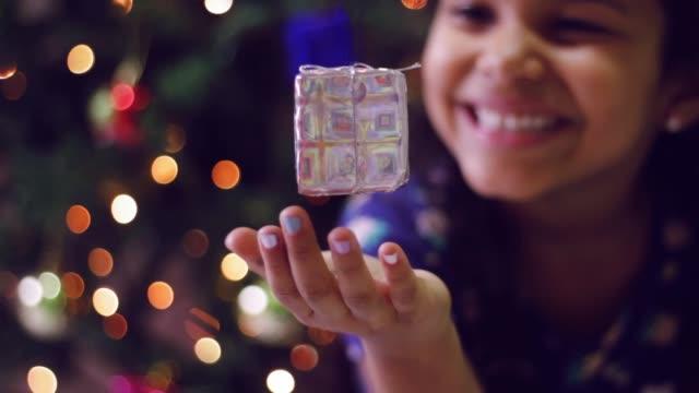 magiska scen av leende flicka att få presentera flytande - fokusera på jul-ljusen i bakgrunden - christmas gift family bildbanksvideor och videomaterial från bakom kulisserna