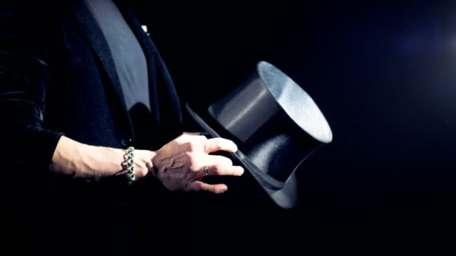 magician is straightening his hat and twisting it in his hands. - cappello video stock e b–roll