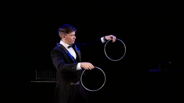 vidéos et rushes de magicien manipule des cerceaux de fer sur thestage - charmeur