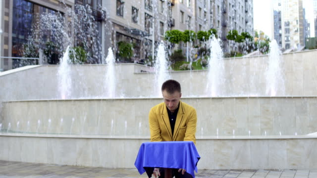 Magician show trick with flying table Magician show focus with flying table. Man stand at the background of fountains at the urban square. Handsome man show focuses for the people at the streets of the city. illusion stock videos & royalty-free footage