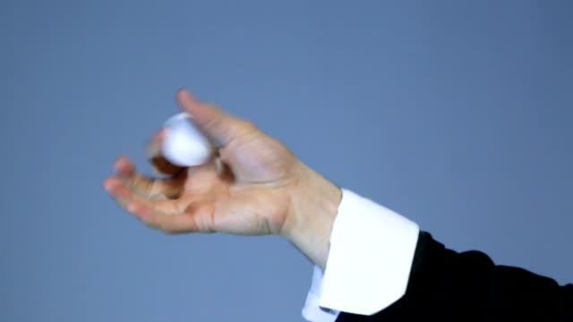 魔術師は、暗い背景に白いボールとトリックを示しています - 豊富点の映像素材/bロール