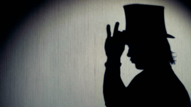 magician silhouette in a top hat showing a trick. close-up. - cilindro video stock e b–roll