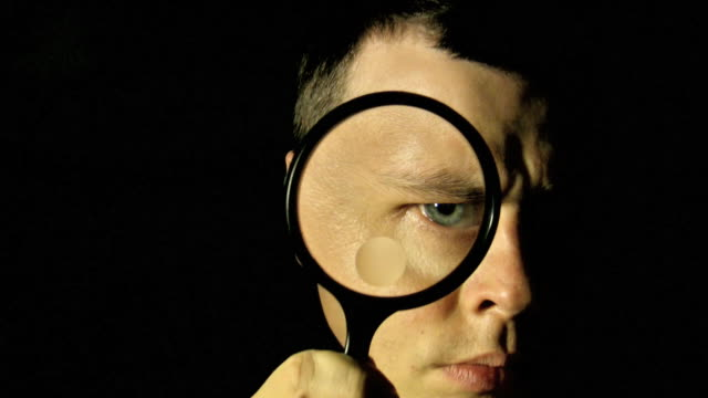 Magnifying Eye V.2 (HD) A man looking through a magnifying glass against black background. (1080i source) magnifying glass stock videos & royalty-free footage