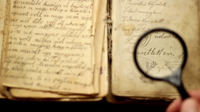 Magnifying glass and vintage book Watching an image in a vintage manuscript with magnifying glass. magnifying glass stock videos & royalty-free footage
