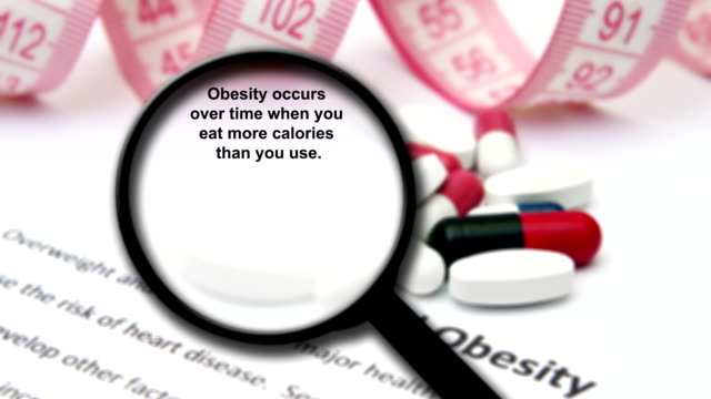 Magnifying glass on overweight and obesity concept video