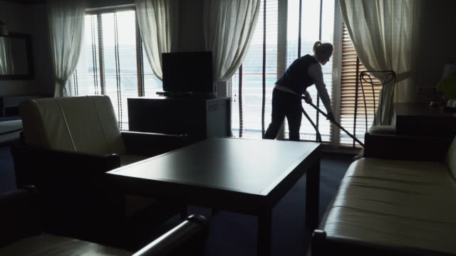 Maid cleans the floor with vacuum cleaner in modern hotel