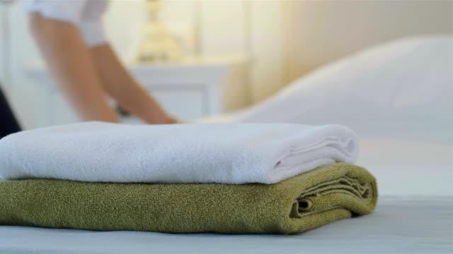 vidéos et rushes de femme de chambre faire le lit dans une chambre d'hôtel, des serviettes propres sur front - main service