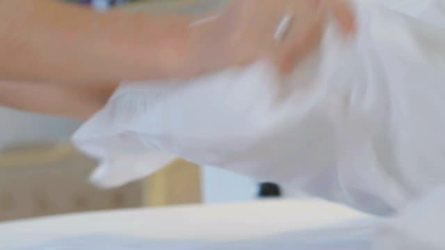 Maid making bed in a hotel room putting a pillow