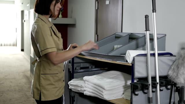 hizmetçi, işleri bir raf üzerinde düzleştirir. - ev temizleme stok videoları ve detay görüntü çekimi