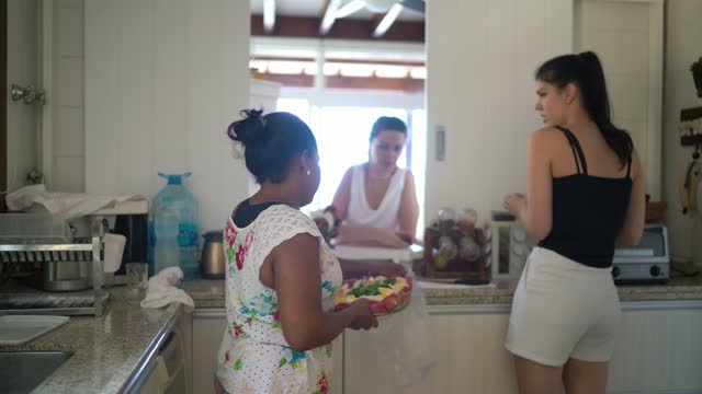 Maid talking to girls in the kitchen at home