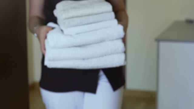 otel odasında toplamaya ve sakinleri için birkaç temiz temiz havlu getiren hizmetçi - ev temizleme stok videoları ve detay görüntü çekimi