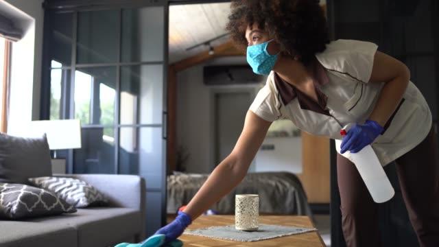 vídeos y material grabado en eventos de stock de sirvienta con una mascarilla facial debido al coronavirus mientras desinfecta una habitación de hotel - hotel
