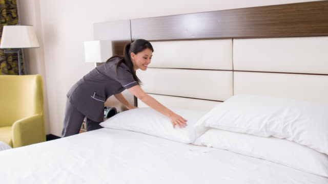 Maid working at a hotel making the bed video