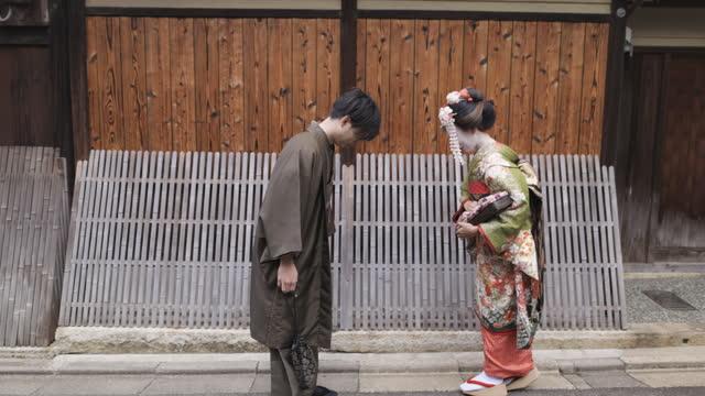 vídeos de stock, filmes e b-roll de maiko (gueixa em treinamento) e um homem em hakama curvando-se na velha rua japonesa - tradição