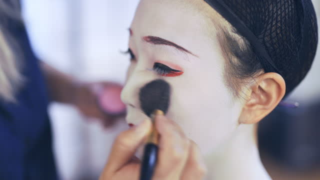 Maiko (Geisha in training) getting special white makeup