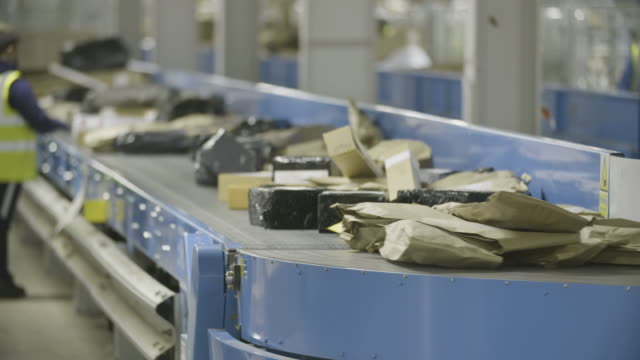 Mail Distribution Centre Packages on a conveyor belt at a postal sorting warehouse. Filmed in 4K on a Sony FS7. post office stock videos & royalty-free footage