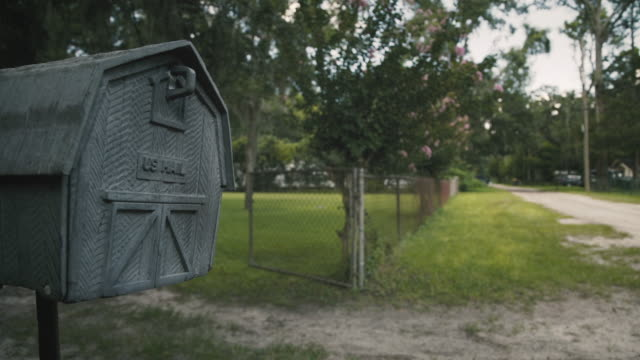 Mailbox on a dirt road Dolly shot of an old mailbox on a dirt road in a low income community. country road stock videos & royalty-free footage