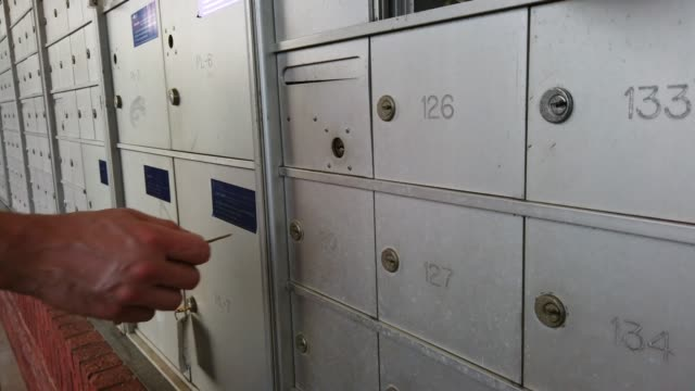 vídeos de stock, filmes e b-roll de uma unidade da caixa postal em um desenvolvimento home do apartamento disparou no movimento lento com uma mão caucasiana dos machos. - correio correspondência