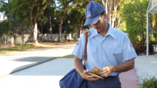 Mailman Walking Along Street Delivering Letters Mailman walks along street carrying letters and looking at houses.Shot on Sony FS700  at frame rate of 25fps post structure stock videos & royalty-free footage