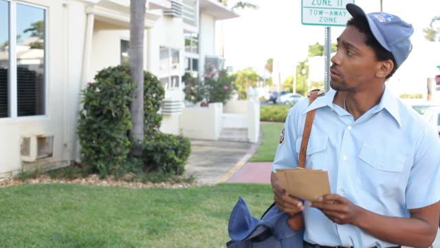 mailman walking along street delivering letters - postal worker 個影片檔及 b 捲影像