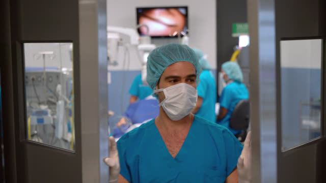 Main surgeon leaving the operating room and opening the door after a successful surgery