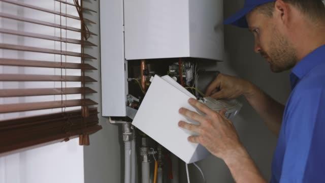 vídeos de stock, filmes e b-roll de manutenção e reparação de serviço de engenharia de trabalho com casa caldeira de aquecimento a gás - servidores