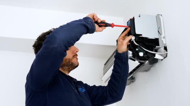 técnico de mantenimiento usa el destornillador en el acondicionador de aire - vídeo