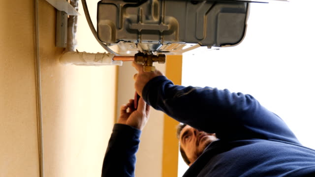 maintenance technician uses the screwdriver on the air conditioner video