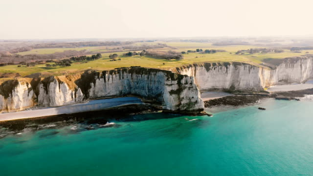 Majestic aerial panning view, azure sea coastline with epic white chalk cliffs and green fields near Etretat, Normandy. Majestic aerial panning view, azure sea coastline with epic white chalk cliffs and green fields near Etretat, Normandy. Idyllic cinematic background drone shot of peaceful pastoral sunset shore. normandy stock videos & royalty-free footage