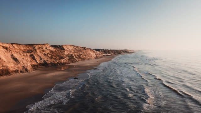 majestic aerial shot of seaside with sandy shores and waves crashing through the beach - danimarca video stock e b–roll