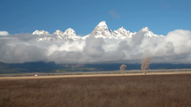 AERIAL: Majestic Grand Teton mountains raising above the foggy clouds in Wyoming video